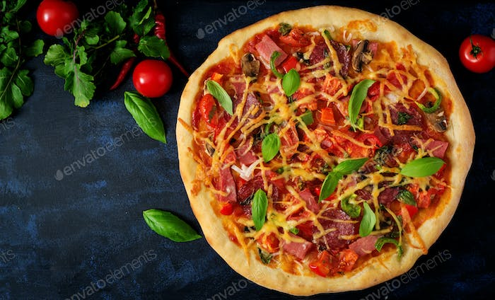 Pizza with salami, ham, tomato, cheese and mushrooms. Top view