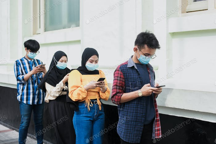 Queue of people with distance and wearing medical mask