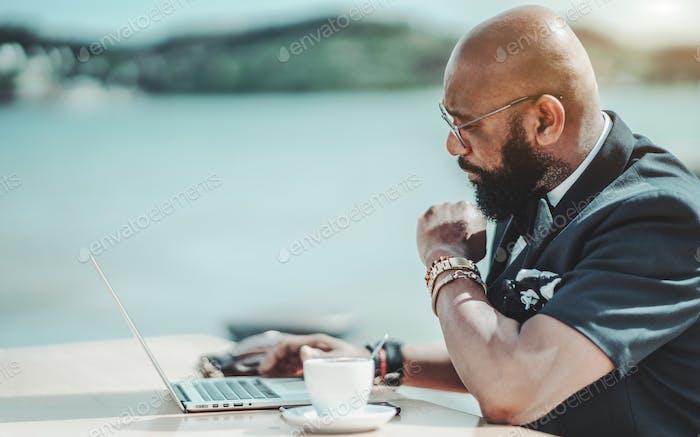 Afrikanischer Geschäftsmann mit einem Laptop