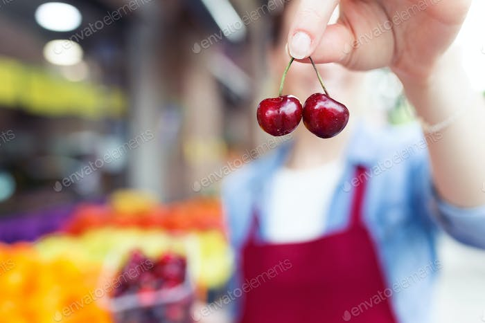 Pretty young saleswoman showing cherries to camera in health gro