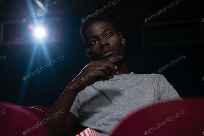 Man having popcorn while watching movie