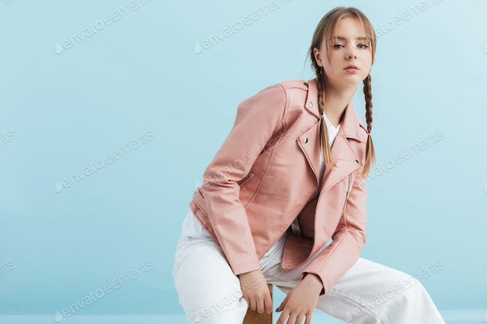 Young attractive girl with two braids in pink leather jacket and