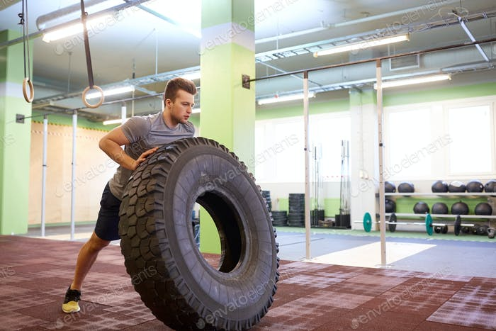 man doing strongman tire flip training in gym