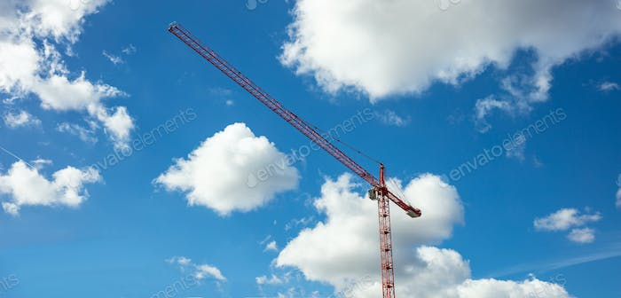 Red tower crane on blue sky background