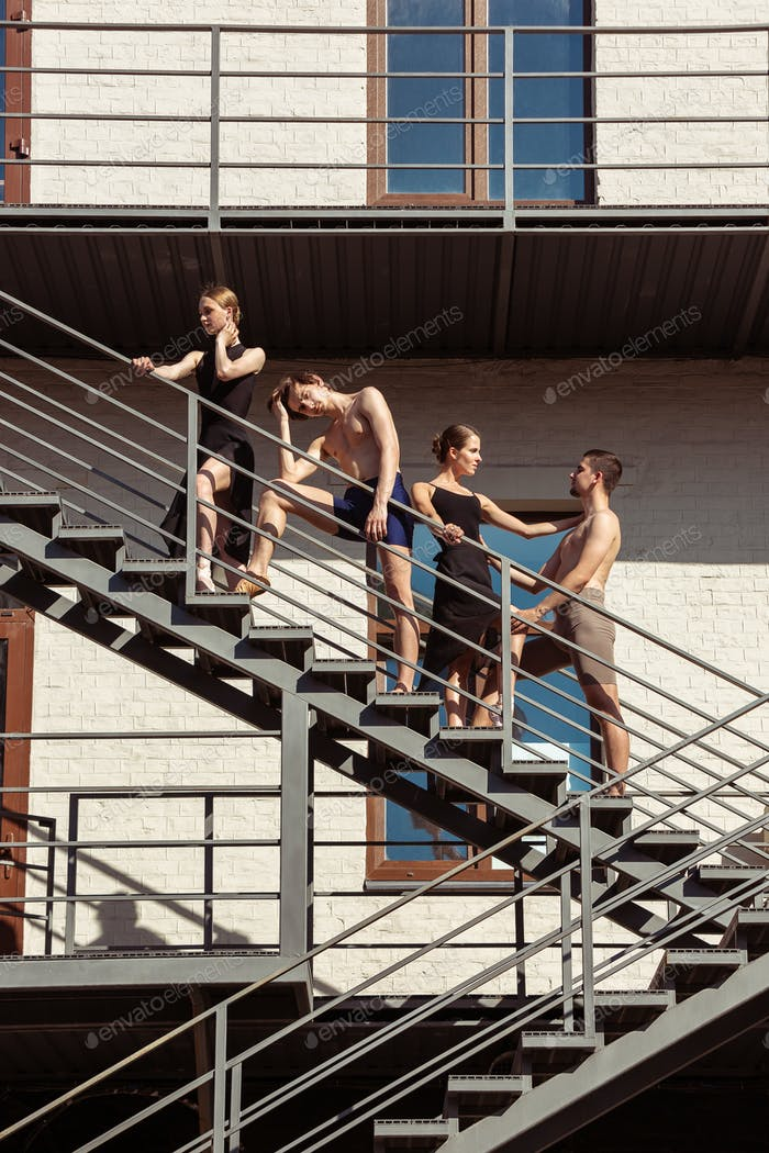 The group of modern ballet dancers performing on the stairs at the city