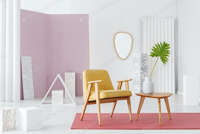 Yellow armchair and wooden coffee table with a vase set in white