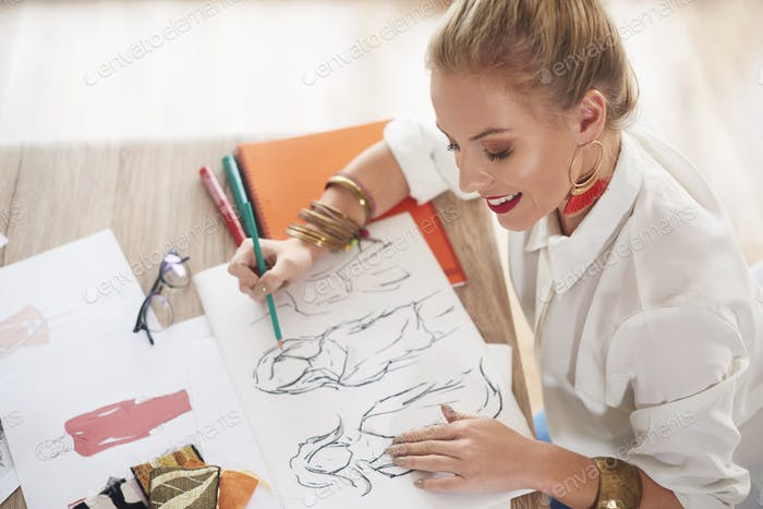 Female design professional sketching at table