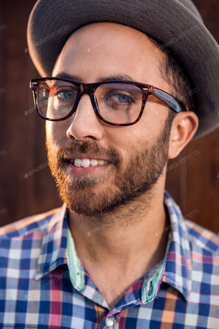 Portrait of creative male professional with eye glasses standing against wall