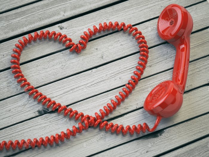 Phone reciever and cord as heart on white wooden background. Lov