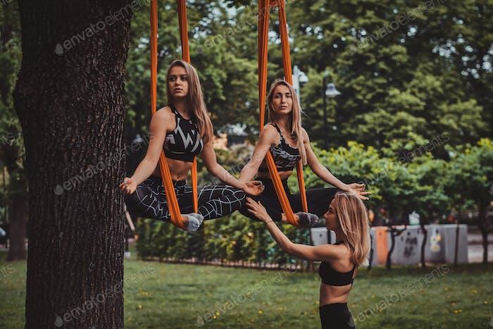 Zwei schöne nachdenkliche Mädchen trainieren mit ihrem Treiner auf den Schlingen