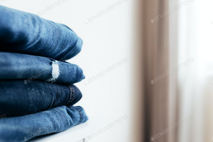 Stack of blue denim jean pants. Textile industry, clothing stores, sale concept.