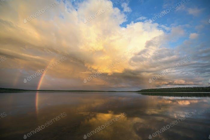 A rainbow and a dramatic cloud formation over a lake.