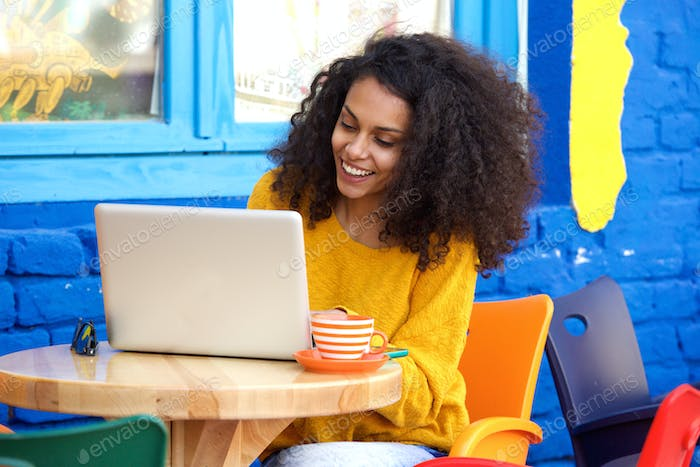 Happy young woman sitting at outdoor cafe using laptop