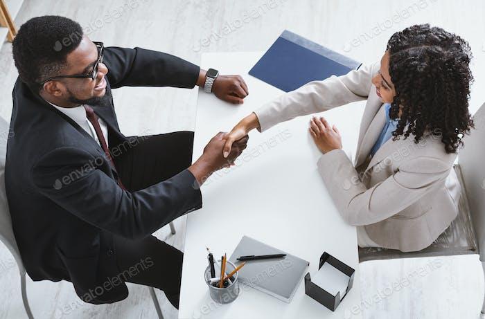 Obige Ansicht des Personalleiters Hände schüttelt mit Stellenbewerber während des Vorstellungsgesprächs im Büro