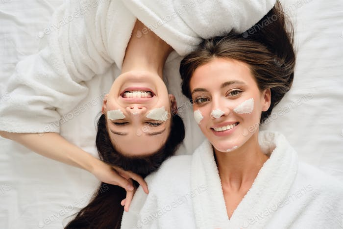 Two smiling women in bathrobes lying in bed with cosmetic mask on faces happily looking in camera