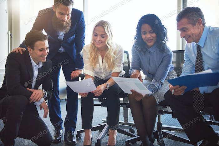 Diverse group of office coworkers discussing paperwork together
