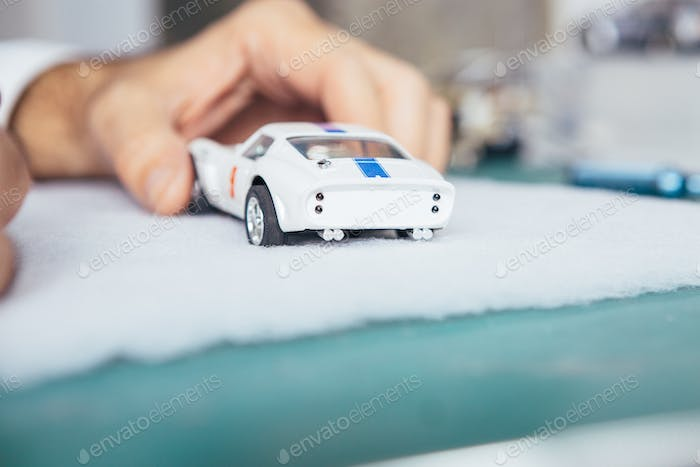 Hands holding slot car
