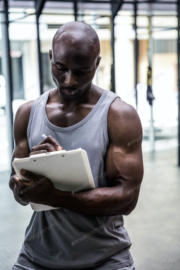 Young bodybuilder writing on a clipboard in the crossfit gym