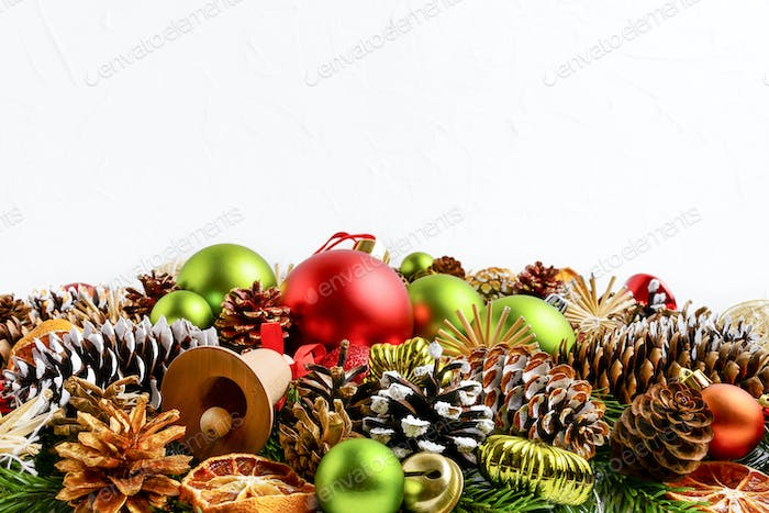 Christmas greeting background with spruce cones and colorful ornaments
