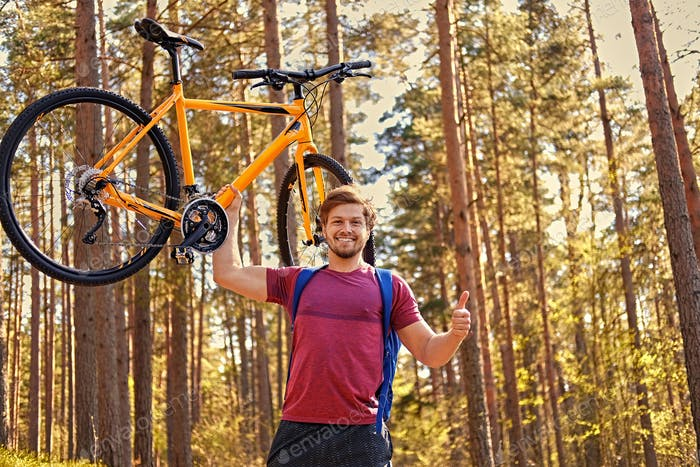 Positive sporty male holds mountain bicycle in one arm.