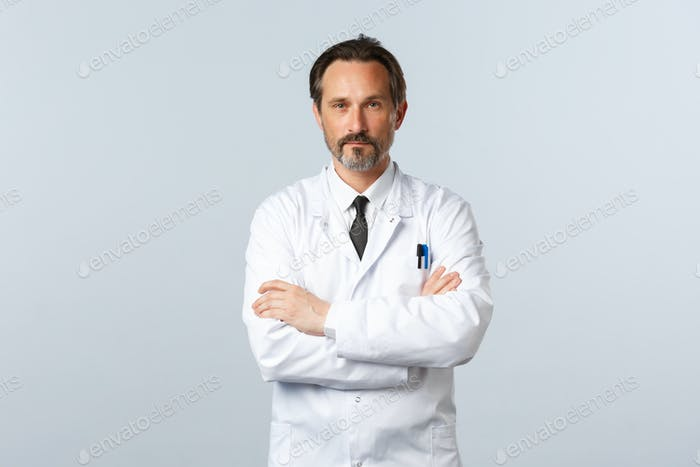 Serious-looking doctor in white coat cross arms chest, looking confident. Treating patients at