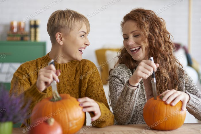 Happy friends preparing decorations for Halloween
