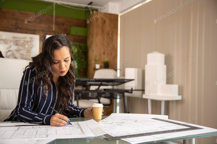 Young female architect working on blue print