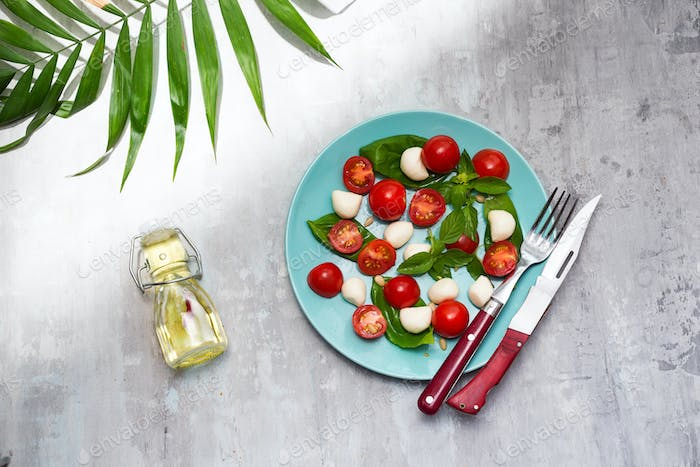 Delicious caprese salad with cherry tomatoes and mozzarella cheese balls with fresh basil leaves