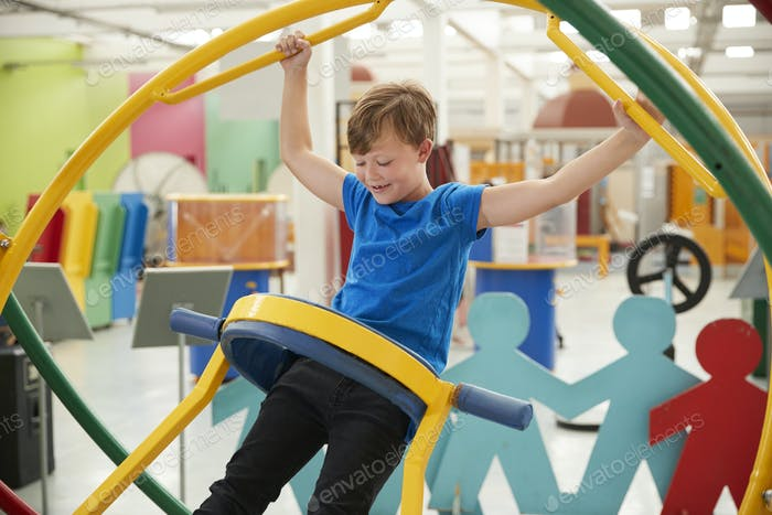 Young white boy in science centre using a human gyroscope