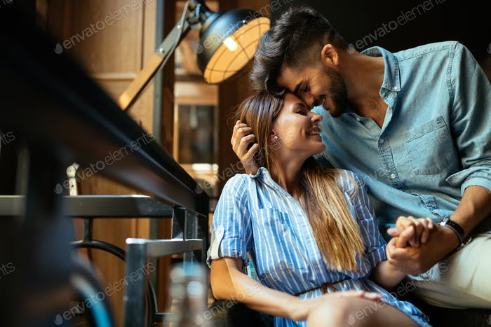 Young attractive couple on date in coffee shop
