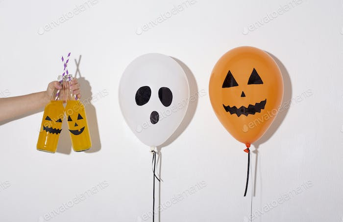 Halloween balloons with drawing faces suggesting to drink cocktails