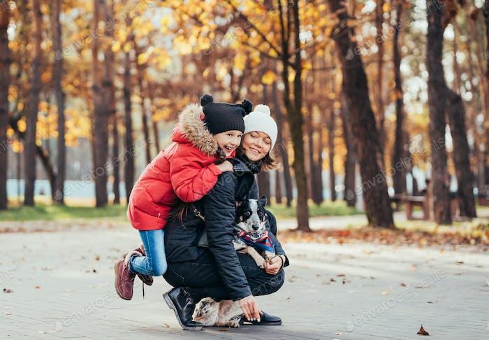 Счастливая мать и дочь играть с собакой в осенний парк
