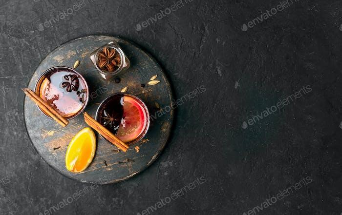 Glühwein mit Orangenscheibe und Gewürzen auf einem hölzernen Hintergrund, Nahaufnahme