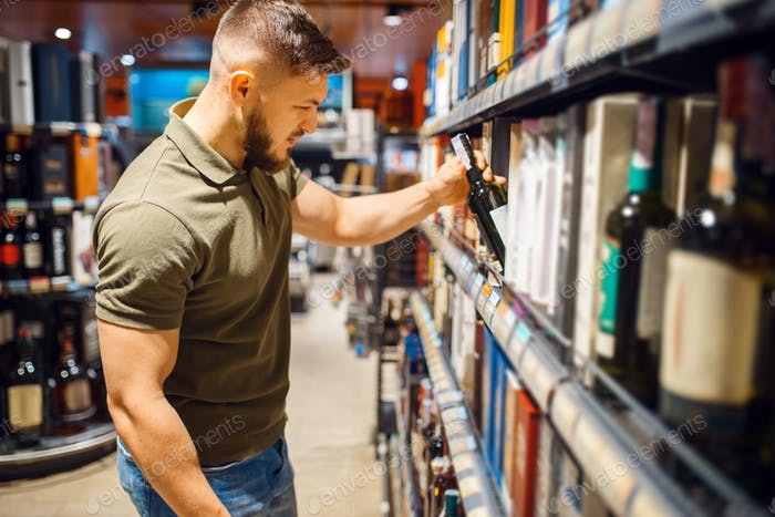 Man choosing alcohol products in grocery store