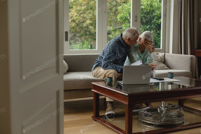 Active senior Caucasian couple calculating bills and feel too sad in living room at home