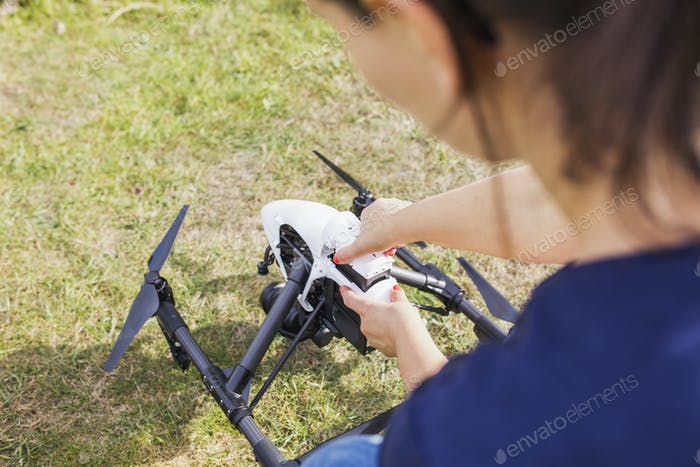 Woman adjusting drone on field