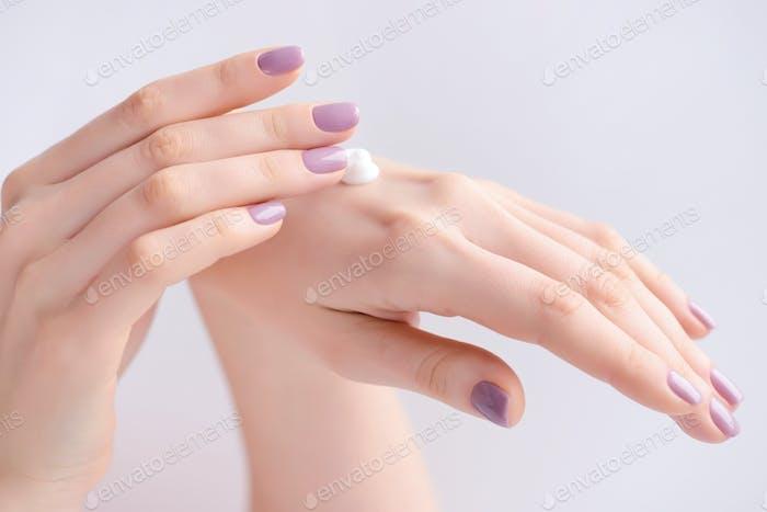 Frauenhände mit rosa Maniküre Creme auftragen. Das Konzept der