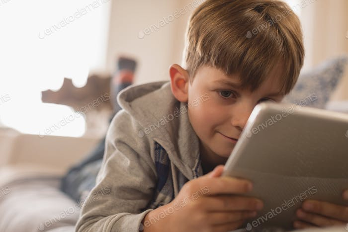 Young Caucasian boy lying on his stomach while using digital tablet in living room at home