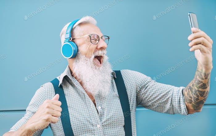 Happy senior man taking selfie while listening music with headphones