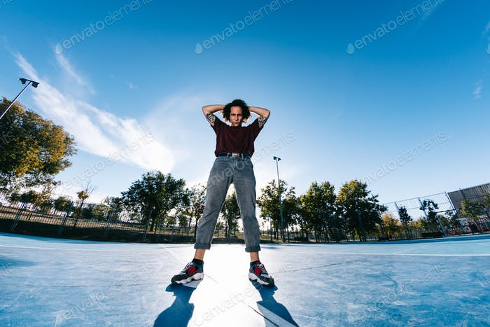 Young cool man break dancer standing in park. Tattoo on body