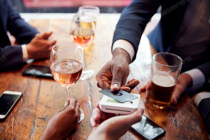 Close Up Of Businessman Paying For Round Of Drinks In Bar After Work Using Contactless Card