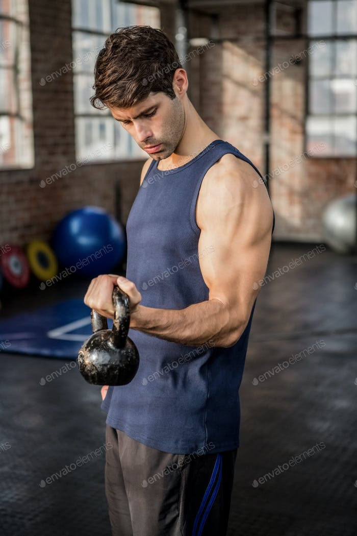 Side view of a man lifting kettlebell at the gym