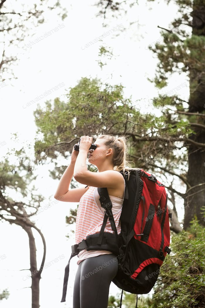 Thumbnail for Blonde hiker looking through binoculars in the nature