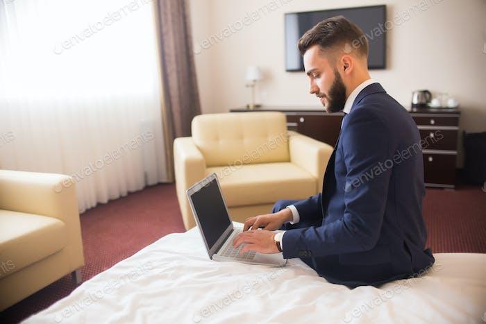 Businessman Using Laptop in Luxury Hotel