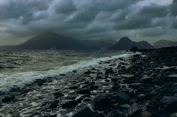 Dramatic landscape coastline view of rocks and Cullin hills, Scotland