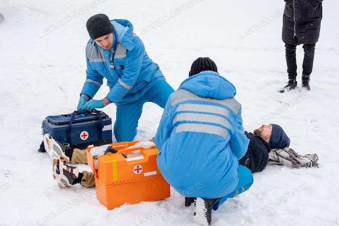Zwei Sanitäter in Uniform geben Erste Hilfe für kranke unbewusste Mann auf Schnee liegend