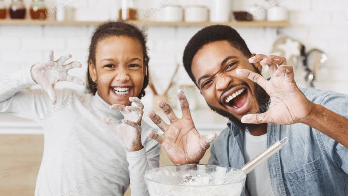 Joyful father and daughter fooling while cooking