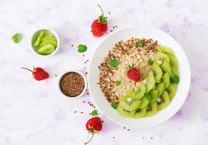 Tasty and healthy oatmeal porridge with kiwi and flax seeds.