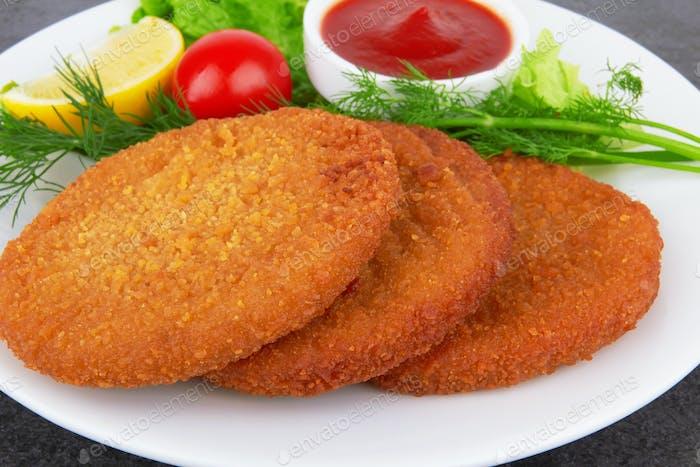 Fischpfannkuchen auf Teller mit Ketchup, auf dunkler Oberfläche