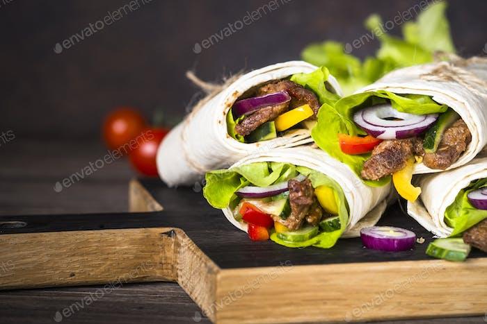 Burritos Tortilla wickelt mit Rindfleisch und Gemüse auf Holzschliessen